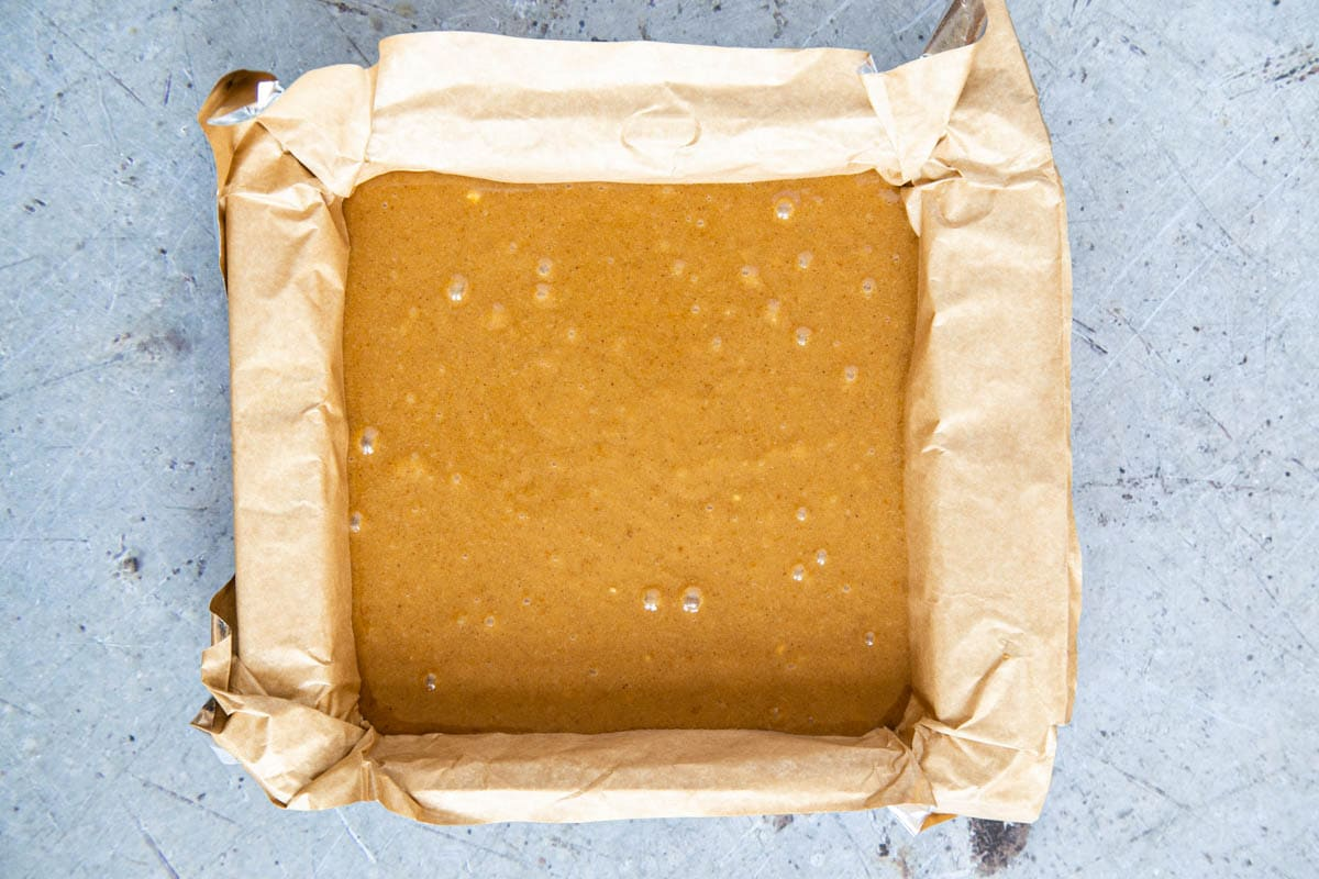 Pumpkin spice blondie batter poured into a lined square baking tray.