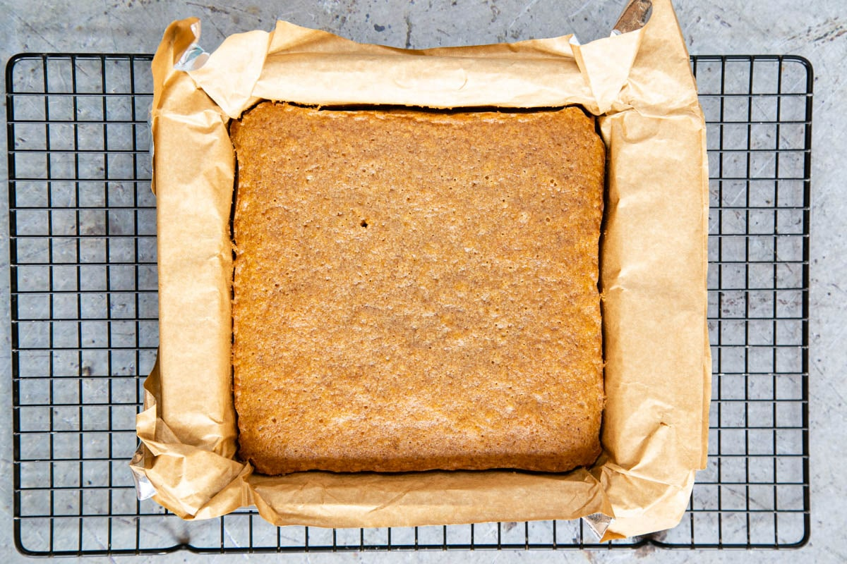 Baked pumpkin spice blondies on a cooling rack, ready to be removed from the pan and the parchment paper removed.