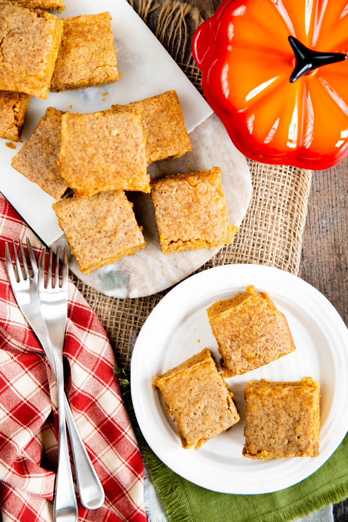 Delicious pumpkin spice blondies, arranged on both a marble board and a side plate. A pumpkin shaped mini casserole dish sits next to the board.