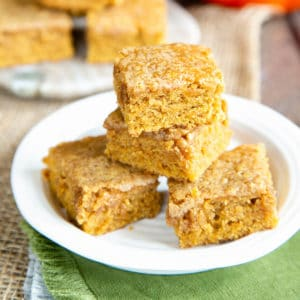 A close up of a stack three hight of yummy pumpkin spice blondies, on a side plate.