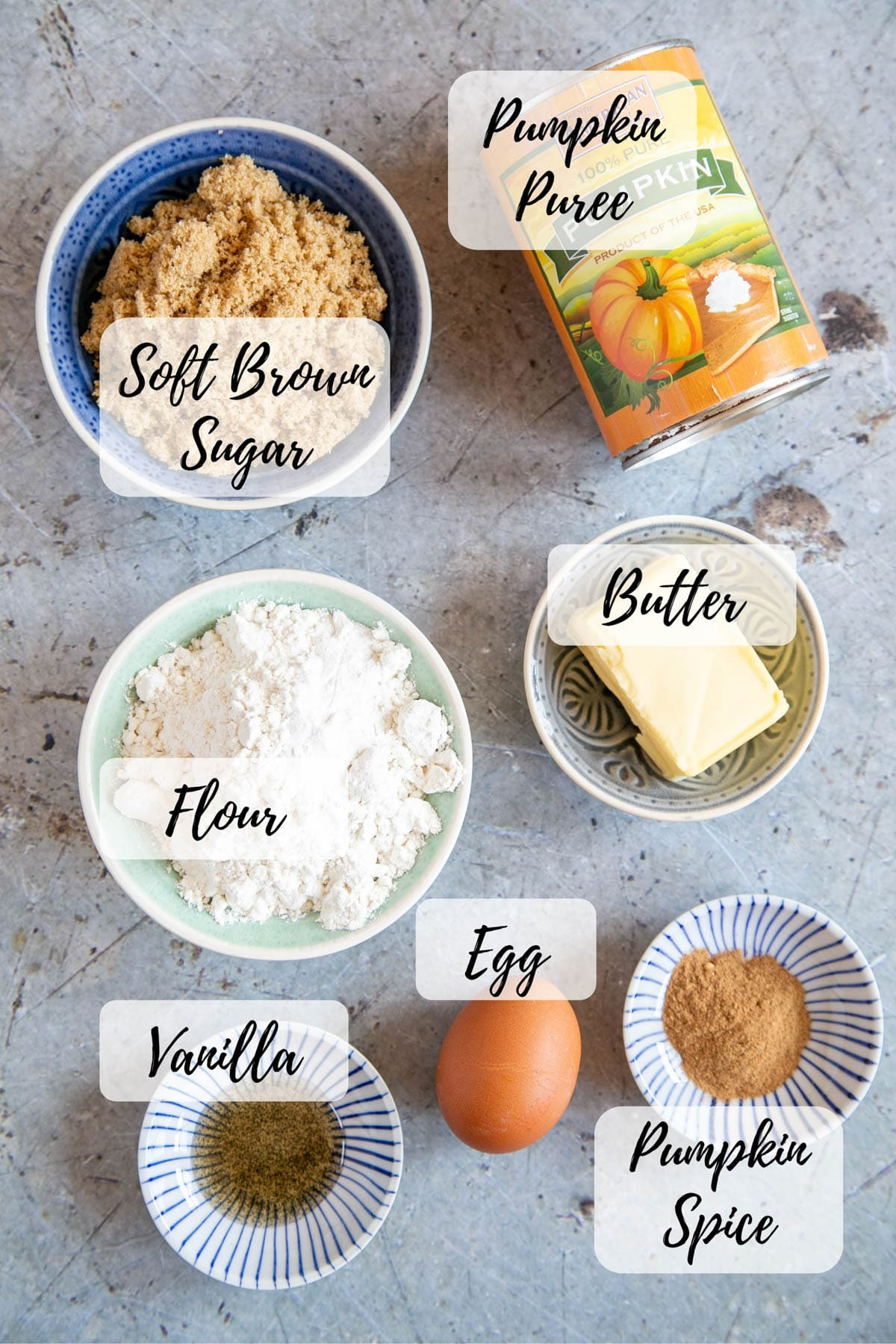 The ingredients for pumpkin blondies: tinned pumpkin puree, soft brown sugar, butter, flour, vanilla extract, pumpkin spice, and an egg.